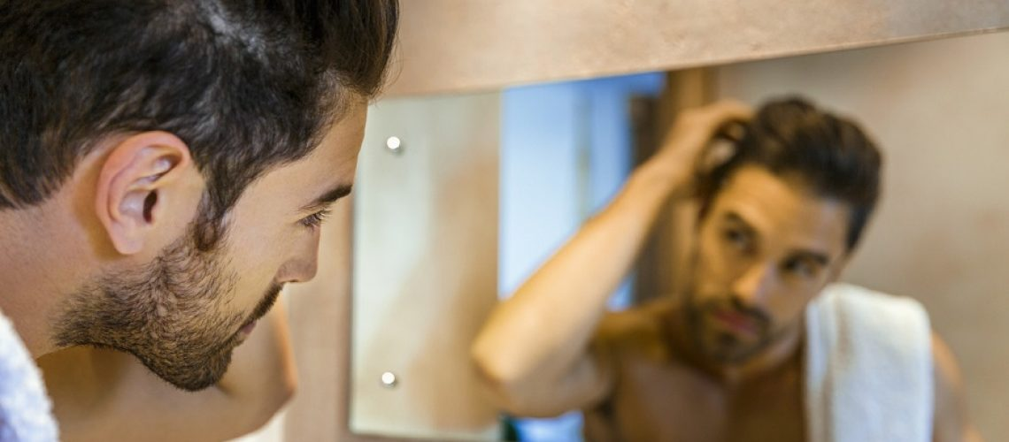 A photo of man examining hair in mirror. He is suffering from hair loss. Shirtless male is in bathroom getting ready for the day. Focus is on him.